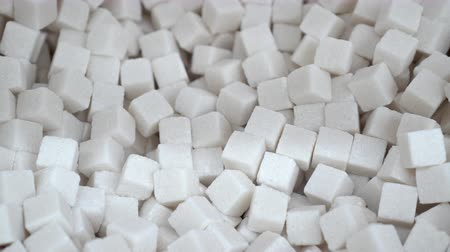 adoçante : A lot of sugar cubes closeup panorama for background of white refined 4K. Sweet cube panning like white death. Background of white refined natural products. Clear place for your isolated text pattern Vídeos