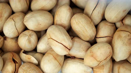 pistacje : A lot of white nut pistachios closeup turning background 4K. Seeds of nut spinning in store for the buyer. Background of pistachios rotating to produce food. Clear place for your isolated text pattern