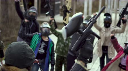paintball : Madman strike warm man into armed rebellion. Group of masked paintball with weapon in their hand close up begin aggressive 4K strike. Evil people in helmet pick up paintball guns anarchist revolution. Stock Footage