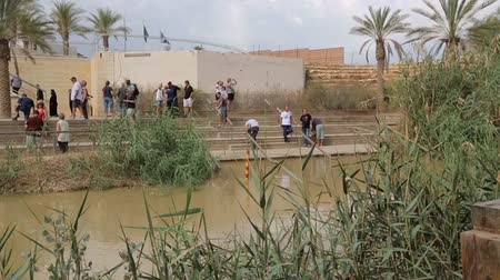 baptismal : Tourists near the Sacred water of the River Jordan. River where Jesus of Nazareth was baptized by John the Baptist. The border between Jordan and Israel. Stock Footage