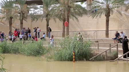 hacı : Tourists near the Sacred water of the River Jordan. River where Jesus of Nazareth was baptized by John the Baptist. The border between Jordan and Israel. Stok Video