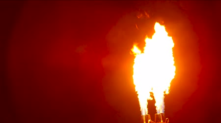 костер : Flames erupt from the turn of two gas burners on a dark background. Flashes of flame. Fire blast is directed from the bottom of the frame vertically upwards on black background. Pulsating flame flare