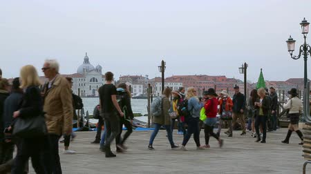 известное место : Venice, Italy - April 2, 2016: Tourists on the pier near the Grand Canal, Venice, Italy. Tourists pedestrians are walking along the frame. Tourists are photographed in famous places.