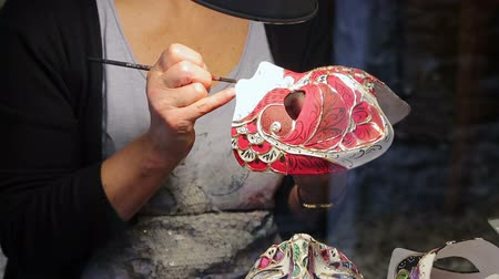glass master : The painting of the Venetian mask with colored paints. Venetian mask creating process in the glass case on the Venetian street. Shooting close-up.