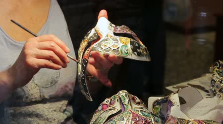 glass master : The painter paints a Venetian mask. Venetian mask creating process in the glass case on the Venetian street. Shooting close-up.