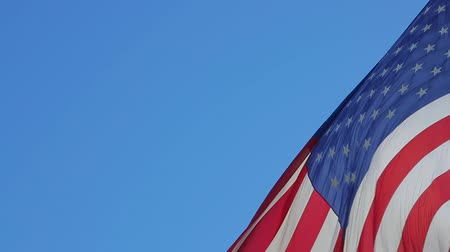 usa independence day : USA flag in the wind. Close-up of an American flag flying in the wind against the background of clear sky. Close up of American flag waving. American concept. Stock Footage