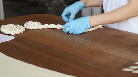 mechanically : Baker prepares decor elements for bread. Baker braids the dough from the dough. Stock Footage