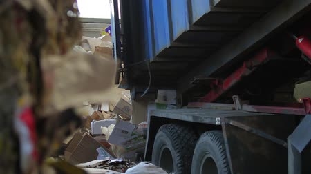 lixo : Truck brought the waste paper to the garbage processing plant. Unloading of recyclable materials in the warehouse of the waste processing plant. Waste paper. Footage with sound.
