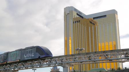 winda : Las Vegas, Nevada - April 2017: Las Vegas monorail train traveling high near the Mandalay Bay hotel and casino. The golden facade of Mandalay Bay sparkles in the rays of the sun. Landscape Las Vegas. Wideo