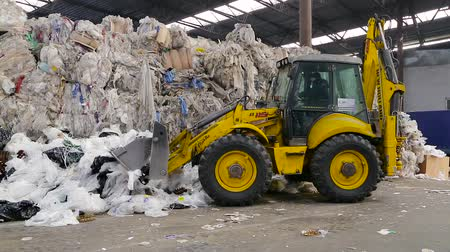 stockpile : Obuhov, Ukraine - Fedruary 2017: Loader sorts the pallets with the recycled material at the waste processing plant. Environment protection concept. Footage with sound.