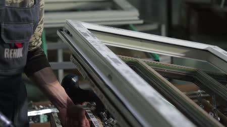 зажимное приспособление : Kyiv, Ukraine - June, 2017: Assembly of plastic and metal windows and doors. Worker installing the fittings to plastic window. Close up shot. Factory for PVC. Workers in workshop. Manufacturing jobs.