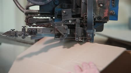 reprocessing : Stapling the carton with staples on the machine. Manufacture of cardboard boxes.