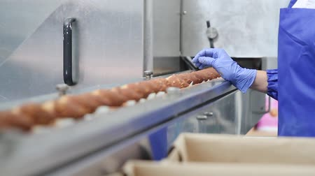 orzechy : Frozen ice cream in a waffle horn is covered with chocolate glaze with nuts. Quality control of the produced ice cream. The employee looks at the ice cream on the conveyor belt.