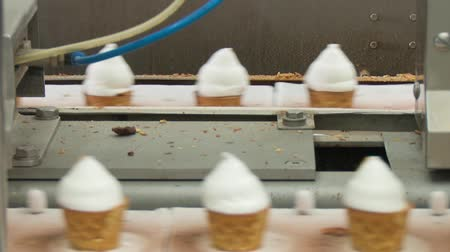 zmrzlinový pohár s ovocem : Ice cream in a cone. Filling of wafer cups with ice cream. Ice cream production line. Vanilla ice cream. Dostupné videozáznamy