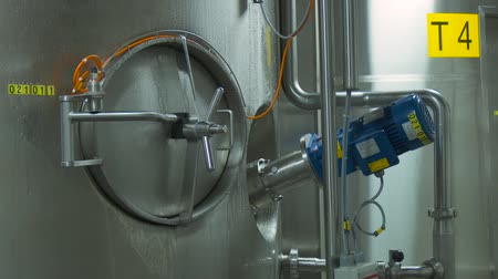 flange : Shiny steel metal pipes and blue engine and valves. Steel tanks in the interior of a modern factory. Steel, modern, shiny pipeline is covered with droplets of condensate. Stock Footage