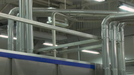 szegecs : Industrial zone, Steel pipelines, valves, cables and walkways. Clean high quality modern pipeline in industrial interior. Pipeline system is made of stainless steel in a modern enterprise. Stock mozgókép