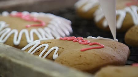 cracknel : Confectioner decorates the gingerbread with cream for Valentines Day. Gingerbread cookies in the form of hearts. Gingerbreads close-up. Confectionary factory. Stock Footage