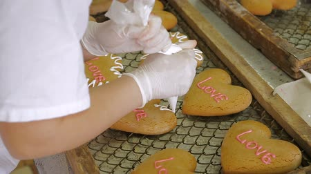 avelã : Confectioner decorates the gingerbread for Valentines Day. Gingerbread cookies in the form of hearts. Gingerbreads close-up, production process. Manufactured gingerbread in confectionery factory. Stock Footage