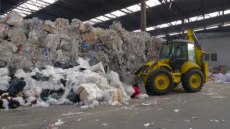 discard : Obuhov, Ukraine - Fedruary 2017: Workers sorting garbage, waste to be processed in a recycling plant. Enviroment protection concept. Warehouses with recyclable materials at garbage processing factory. Stock Footage