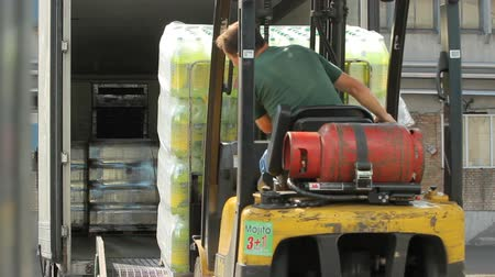 отправка : Kiev, Ukraine - May 2017: Forklift loads the packaging with drinks in plastic bottles into the trailer of the lorry. Forklift truck loading a truck. Pallet with drinks in plastic bottles in warehouse.
