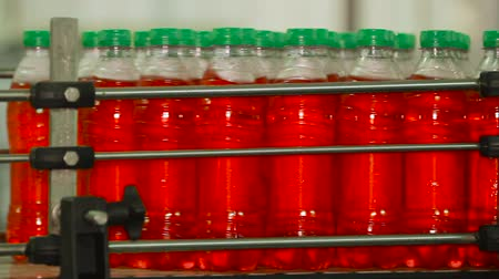 suco : Lemonade bottle conveyor industry. Production line for bottling bottles. Bottling of juice in plastic bottles.