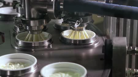 cheese packaging : Production of yogurt in a dairy factory, industrial equipment for filling in plastic cups. Unit for pouring yoghurt into plastic jars at a dairy factory. Equipment at dairy plant. Stock Footage