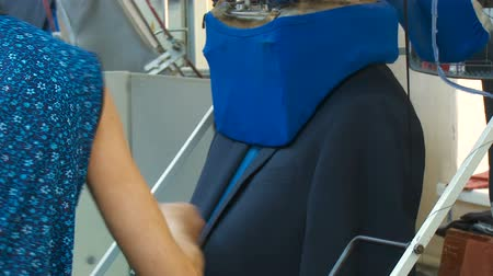 presser : Woman ironing a mans jacket with a professional iron in a clothing factory. Automatic ironing at the factory. Conveyor for ironing. Sewing factory. Business suit Stock Footage