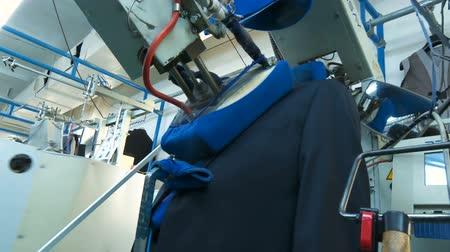 presser : Automatic ironing at the factory. Conveyor for ironing. Ironing professional. Presser in sewing clothes pressed, bottom view. Automated process of ironing clothes. Sewing factory.