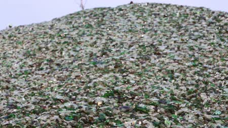 smashing : Mountain of glass broken multicolored bottles. Glass broken bottles in recycling industry factory. Crushed of recycled glass bottles at factory. Recycling of waste from glass bottles. Panning. Stock Footage