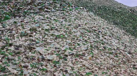 shattered : Mountain of glass broken multicolored bottles. Glass broken bottles in recycling industry factory. Crushed of recycled glass bottles at factory. Recycling of waste from glass bottles. Panning. Stock Footage