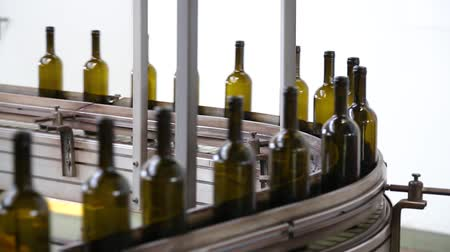виноделие : Wine bottles moving along a conveyor belt in a wine bottling factory. Bottle production line. Technological line for bottling of wine. Production of glass wine bottles. Ambient sound at factory.