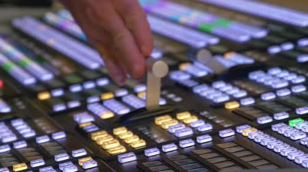 enstrüman : Professional modern broadcasting console. Pushes the handle console in mobile television station telecruiser. TV editor working with video and audio mixer.
