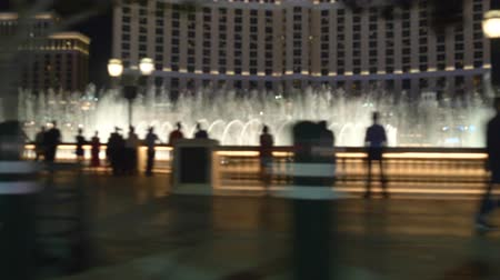 bellagio : Las Vegas strip driving shot at night. Car drives near famous fountain show in Las Vegas. Blurred out of focus video. Background video. Stock Footage