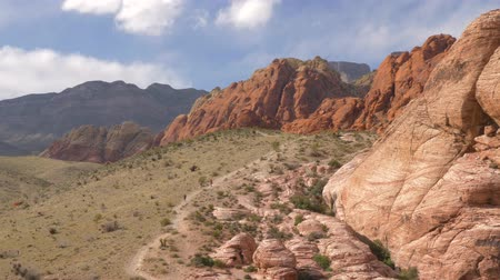 rocks red : People walk to Red Rock Canyon Nevada Las Vegas. Tourists hiking in Red Rock Canyon, Nevada, USA. Camera Pans - Red Rock Canyon Nevada. Scenic view, Red Rock Canyon State Park, Nevada, USA. Stock Footage