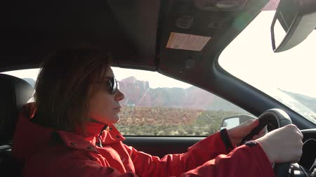 дама : Young woman is driving a car on a sunny day, outside the window is a mountain landscape the Red Rock Canyon. Woman in a red jacket driving, close up. woman with a serious look driving a car. Стоковые видеозаписи