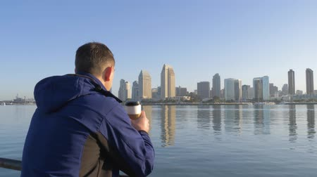 barışçı : Man drinking coffee at morning on San Diego City and looks at cityscape of downtown. Man in his hand is holding blank paper cup in city landscape background. View from back. View of downtown San Diego