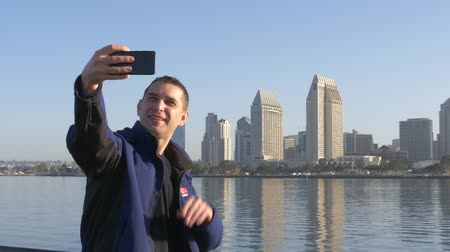enredo : Young male blogger writes a story for his blog about traveling. Blogger online report about his trip to San Diego. Selfie shooting on phone on the background of big city in USA. Social network concept