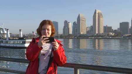 selfie girl : Young woman take selfie from hands with phone on San Diego city pier. Natural young girl taking selfie with her mobile phone near downtown San Diego. Happy traveler woman is taking selfie.