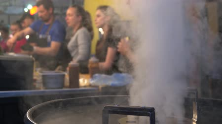 cozinhar : Food sellers and cooks are behind the counters in the background are out of focus. In the foreground, thick steam from the boiling cauldron flows upward. Festival of street food. Stock Footage