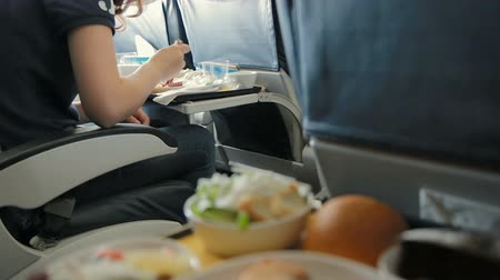 aircraft cabin : Food class on the table. Young women having a meal on the board. Tray of food in the airplane. Tray of food on the plane, business class travel. Stock Footage
