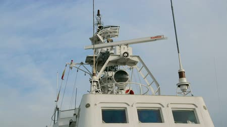 ориентация : Antenna of radar on deck of a modern military ship. Ships antenna and navigation system in a clear sky. Rotation of radar on upper deck of warship. Navigation and radar equipment and antenna on ship.
