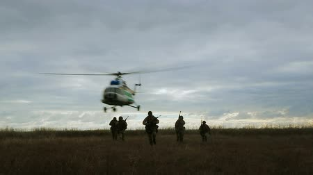 commando : Special Forces landed from a helicopter and advanced to special mission across the field. The landing of special forces at dusk. Silhouettes of soldiers running across the field.