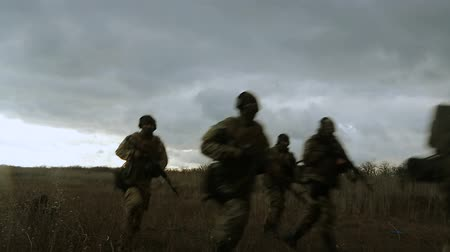 bojiště : Special Forces landed from a helicopter and advanced to special mission across the field. The landing of special forces at dusk. Silhouettes of soldiers running across the field.