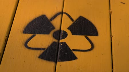 ionizing : Sign of radiation on a yellow wooden board. Radioactive sign - symbol of radiation. Yellow and black radioactive hazard (ionizing radiation) nuclear danger warning symbol. Stock Footage