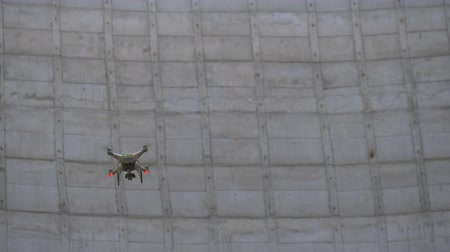 Drone tracking at a construction site. Drone flies between building structures. Drone is involved in the construction of industrial buildings. Drone flies against a concrete wall.