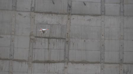 Drone flies between building structures. Drone tracking at a construction site. Drone is involved in the construction of industrial buildings. Drone flies against a concrete wall.