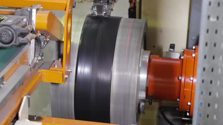 Tire manufacture robotic equipment on tire building plant at works. The rubber tape is reeled up on a drum in the machine. Tire production machine close up. Manufacture of tires. Stock Footage