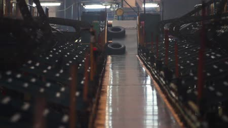 Conveyor belt feeds tires for sorting and checking. Process of forming tires in a factory. Manufacture of tires. Tyre production machine conveyor. Automotive wheel molding in a factory.