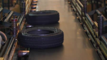 Automotive tires move down on the conveyor belt after curing pressing at the rubber factory. Tire moves on the conveyor to the sorting warehouse. Finished tires on the conveyor are fed to warehouse. Stock Footage
