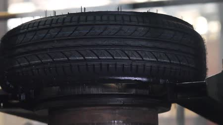 Car tires production. Hot, smoked tires after molding arrive on the conveyor. Manufacture of automobile tyres. Vulcanization of tires at high pressure and temperature. Stock Footage